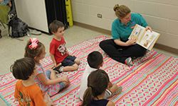 A lady reading a story book to kids